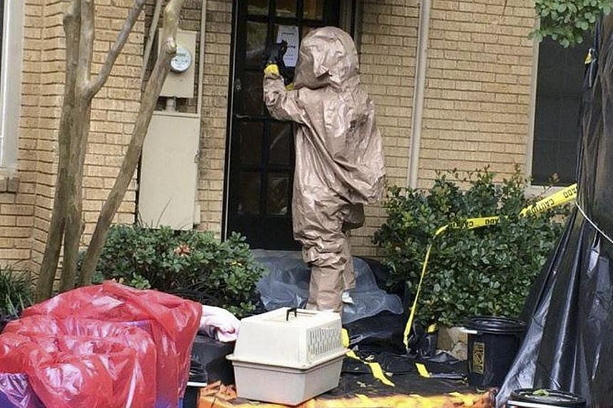 A man wearing a hazardous material suit prepares to remove Bentley from the home of Ebola patient Nina Pham, in this handout picture released by the City of Dallas, Texas on Oct 13, 2014. -- PHOTO: REUTERS