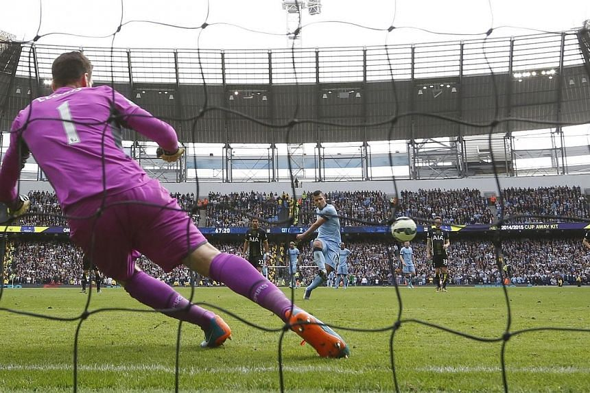 Manchester City's Sergio Aguero scores his third goal from the penalty spot during their English Premier League soccer match against Tottenham Hotspur at the Etihad Stadium in Manchester, northern England on Oct 18, 2014. -- PHOTO: REUTERS