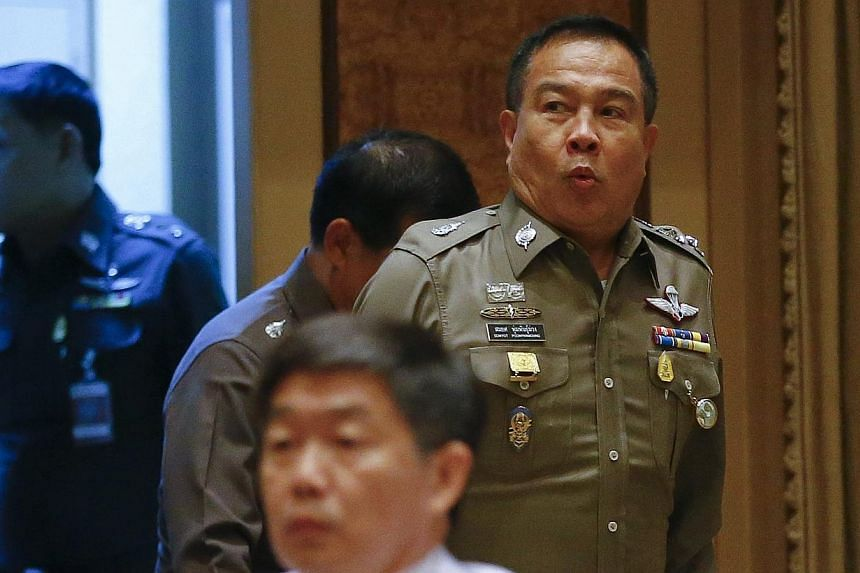 Chief of Royal Thai Police General Somyot Poompanmuang (right) reacts as he arrives to address reporters in Bangkok on Oct 7, 2014. Thailand has agreed to allow British police to join an investigation into the murder of two backpackers on a Thai