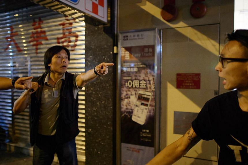 A policeman (left) shouts at a pro-democracy protester following a scuffle in the Mong Kok district of Hong Kong, on Oct 18, 2014. -- PHOTO: AFP
