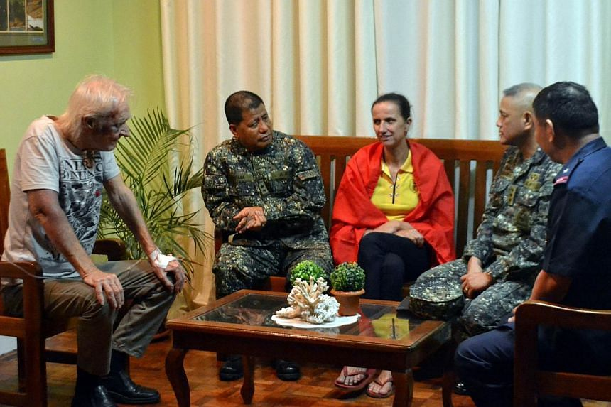 The two Germans kidnapped by Islamic militants, Stefan Okonek (left) and his partner Henrike Dielen (third from right) speaking to Philippine military and police officials in Zamboanga City, on Mindanao, after their release.