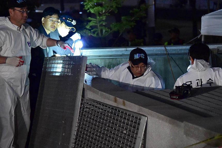 South Korean National Forensic Service members check a broken ventilation grate after concertgoers fell through it into an underground parking area below in Seongnam City, south of Seoul on Oct 17, 2014. -- PHOTO: AFP