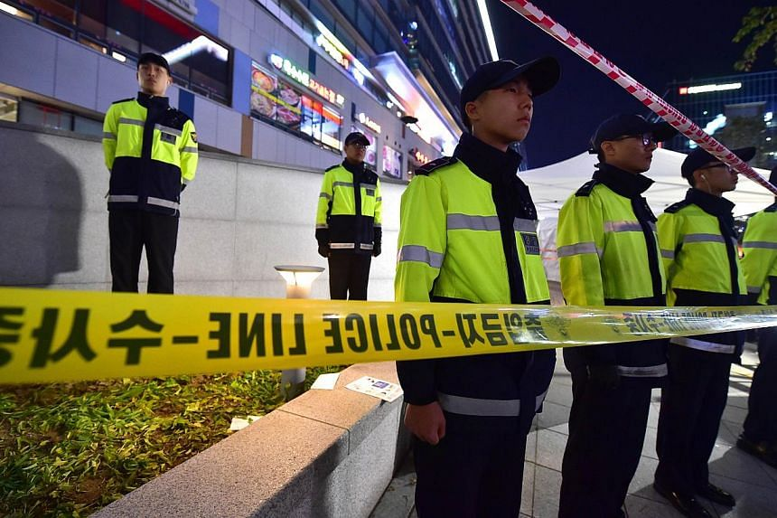 Policemen stand guard near a broken ventilation grate after concertgoers fell through it into an underground parking area below in Seongnam City, south of Seoul on Oct 17, 2014. -- PHOTO: AFP