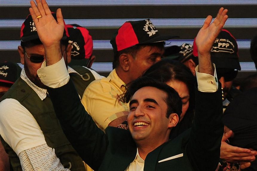 Bilawal Bhutto Zardari (centre) waves to supporters during his arrival for a public gathering in Karachi on Oct 18, 2014. Tens of thousands of supporters gathered in Karachi to hear the son of the country's slain premier Benazir Bhutto, on the formal