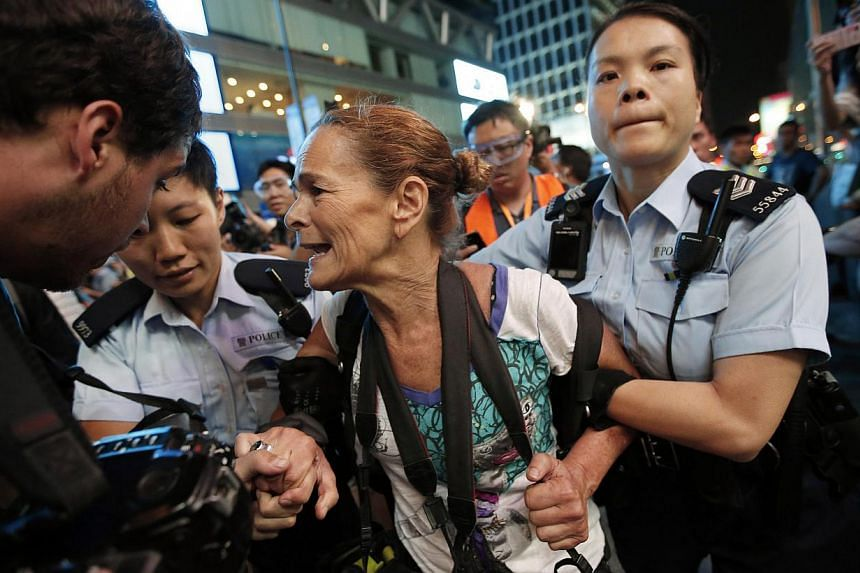 Police officers detaining Getty Images photographer Paula Bronstein during a confrontation between police and pro-democracy protesters at Mongkok shopping district in Hong Kong on October 17, 2014. Hong Kong riot police used pepper spray and baton ch