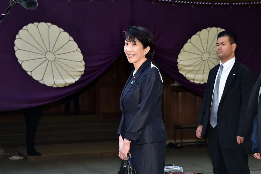 Japanese Internal Affairs and Communications Minister Sanae Takaichi (left) speaking to reporters as she visits the controversial Yasukuni Shrine in Tokyo for the shrine's autumn festival on October 18, 2014. -- PHOTO: AFP
