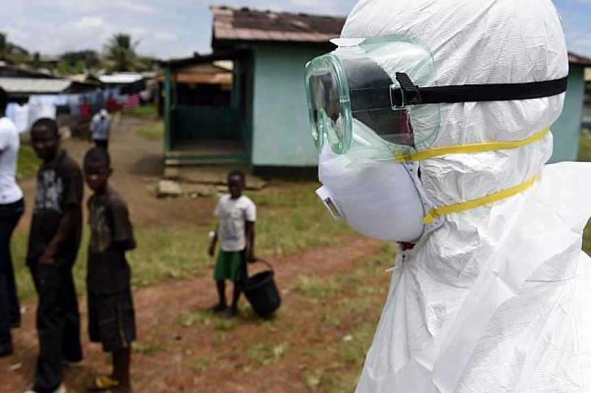 Children look on as a Red Cross worker makes his way to collect a body of a person suspected of dying from the Ebola virus, from a house in the Center Street neighborhood of the Liberian capital Monrovia, on Oct 4, 2014.Children in Liberia, Sie