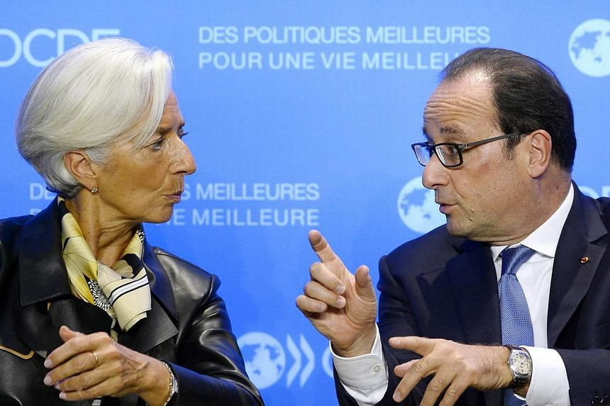 International Monetary Fund managing director Christine Lagarde (left) speaks with French President Francois Hollande during an OECD meeting in Paris, on Oct 17, 2014.Lagarde said Friday the plunge in global stock exchanges this week was due to