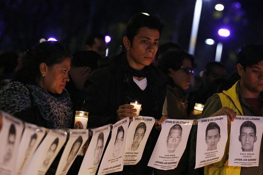 Protesters and members of Amnesty International hold photographs of missing students outside the building of the office of Mexico's Attorney-General, during a protest supporting the Ayotzinapa Teacher Training College missing students, in Mexico City