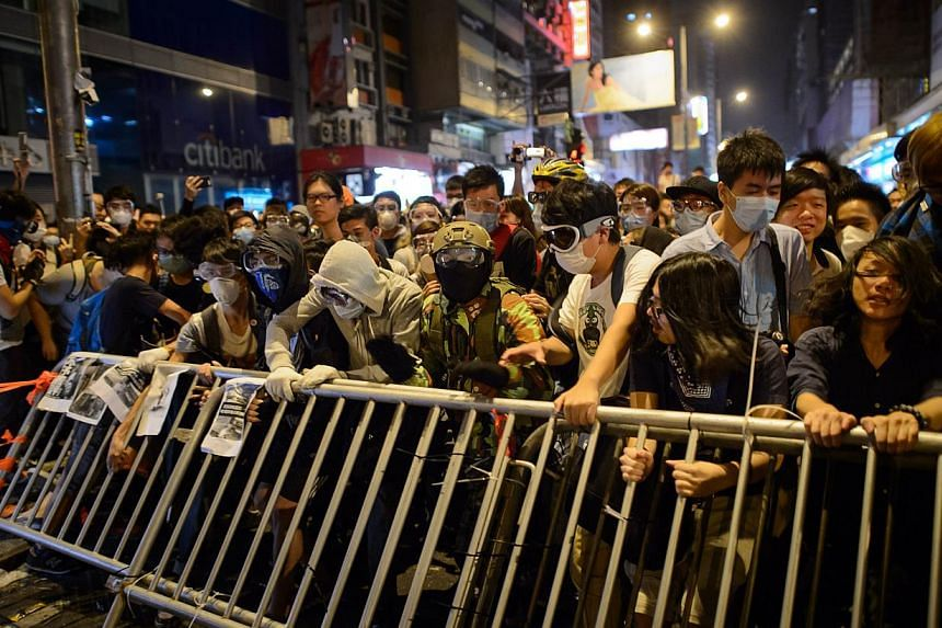 Pro-democracy protesters remove barriers before clashing with police on a road in the Mong Kok district of Hong Kong early on Oct 19, 2014. -- PHOTO: AFP