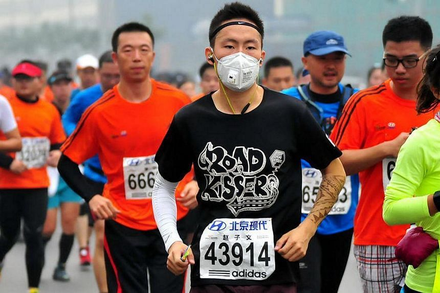 A runner wears a mask as he takes part in the 34th Beijing International Marathon which began at Tiananmen Square in Beijing on Oct 19, 2014, with many of the tens of thousands of participants wearing face masks, as the 42-kilometer course ended at t