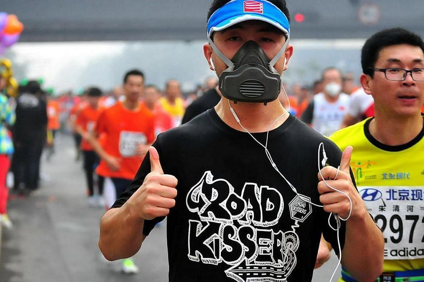 A runner wears a gas mask as he takes part in the 34th Beijing International Marathon which began at Tiananmen Square in Beijing on Oct 19, 2014, with many of the tens of thousands of participants wearing face masks, as the 42-kilometer course ended