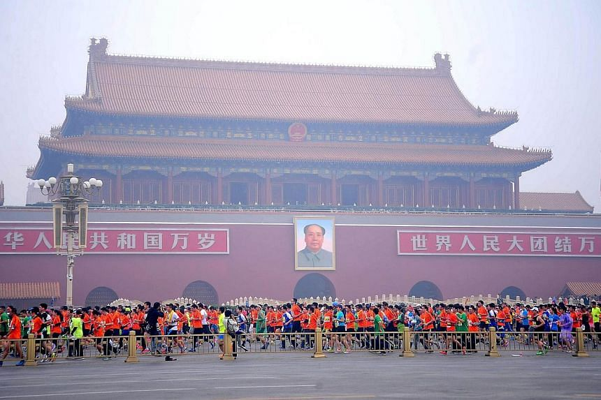 Runners take part in the 34th Beijing International Marathon which began at Tiananmen Square in Beijing on Oct 19, 2014, with many of the tens of thousands of participants wearing face masks, as the 42-kilometer course ended at the Olympic Park. -- P