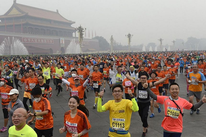 Participants run past the Tiananmen gate with a portrait of China's late leader Mao Zedong on a hazy day during the Beijing International Marathon in Beijing on Oct 19, 2014. -- PHOTO: REUTERS