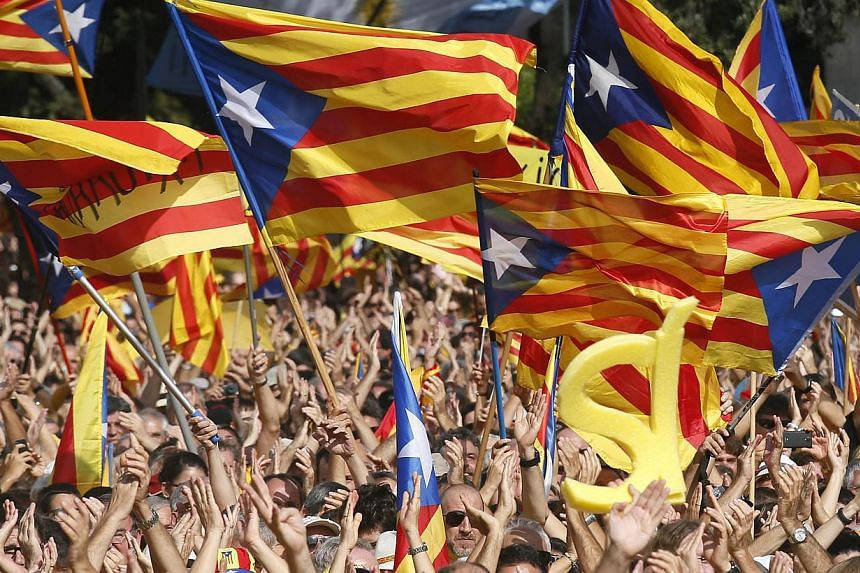 """People wave their """"Esteladas"""" (Catalonian separatist flag) flags during a Catalan pro-independence demonstration at Catalunya square in Barcelona on Oct 19, 2014.Tens of thousands of Catalans crowded central Barcelona on Sunday calling for earl"""