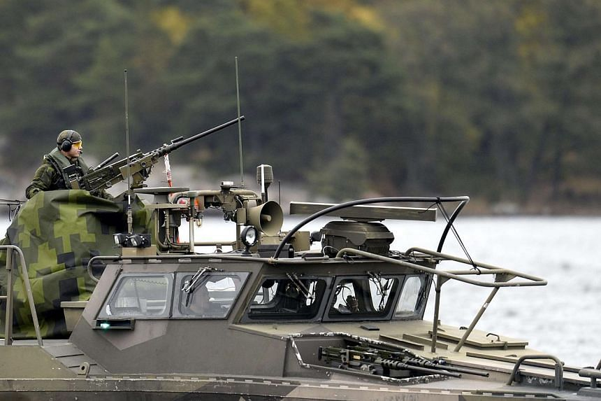 """Crew members onboard a Swedish Navy fast-attack craft stand guard at the Stockholm archipelago, in Sweden, on Oct 18, 2014.Mystery deepened on Sunday over a Swedish military operation triggered by """"foreign underwater activity"""" off the coast of"""