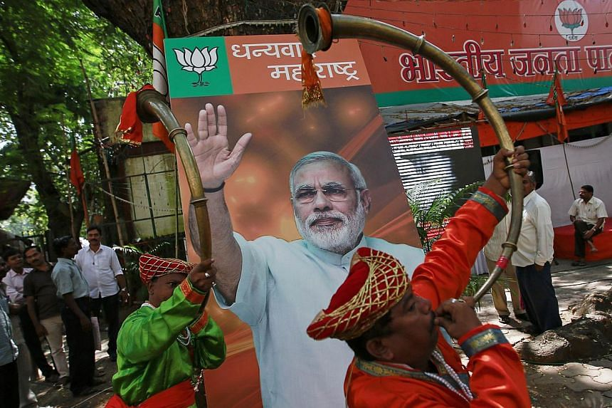 Musicians play instruments in front of the portrait of Indian Prime Minister Narendra Modi, outside the Bharatiya Janata Party (BJP) party office in Mumbai on Oct 19, 2014. -- PHOTO: REUTERS