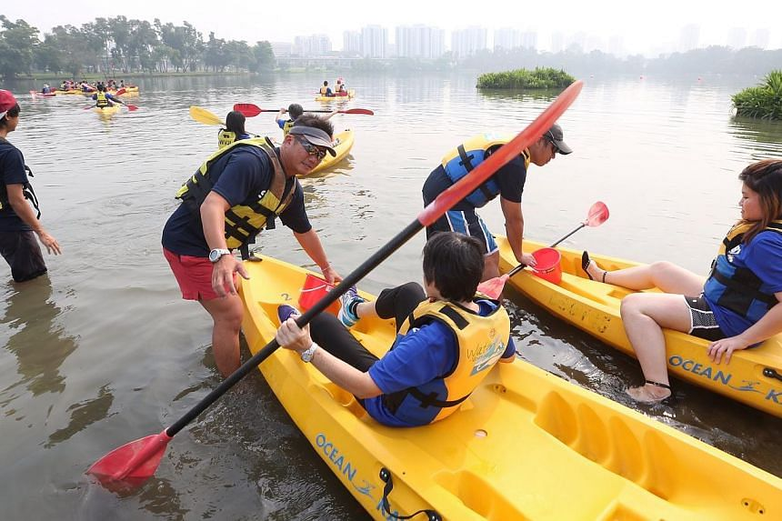Facilitators help members of the public into the kayaks as they use pails to pick up rubbish as part of a clean-up of Jurong Lake Park on Oct 19, 2014. -- ST PHOTO: NEO XIAOBIN