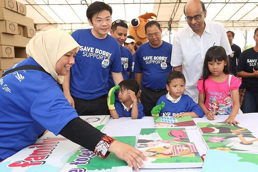 Deputy Prine Minister Tharman Shanmugaratnam (in white), Minister for Culture, Community and Youth Lawrence Wong (second from left), and Minister of State for National Development Desmond Lee (third from left) join members of the public at a puzzle b