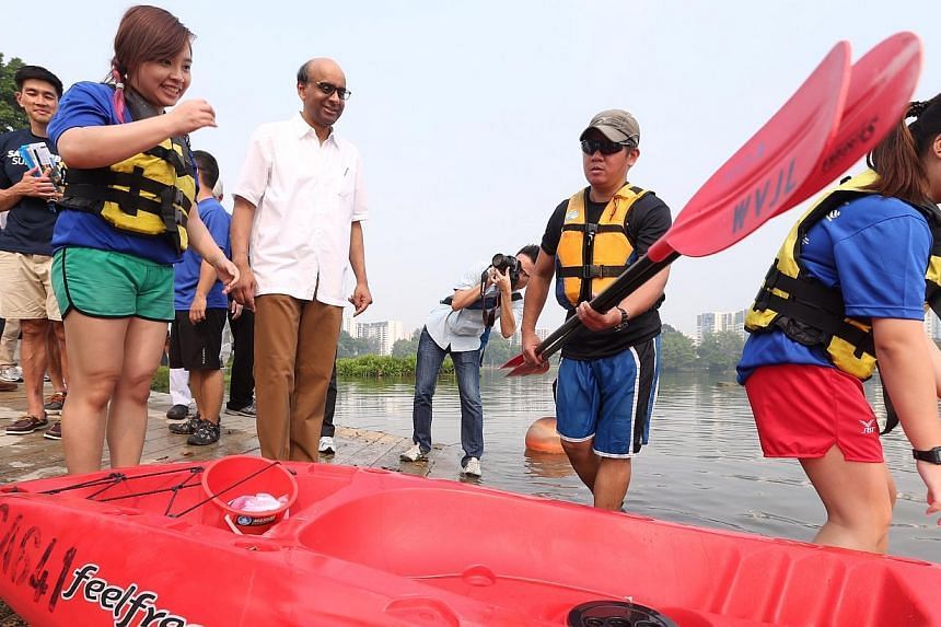 Mr Tharman (in white) watches as members of the public head out on kayaks with pails to pick up rubbish as part of a clean-up of Jurong Lake Park on Oct 19, 2014.-- ST PHOTO: NEO XIAOBIN