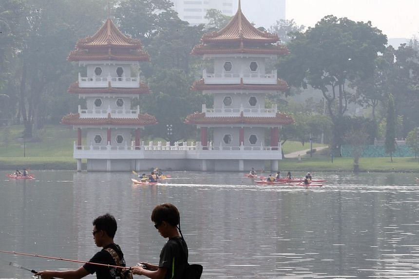 Two boys fish as members of the public in kayaks clean up Jurong Lake Park on Oct 19, 2014.-- ST PHOTO: NEO XIAOBIN