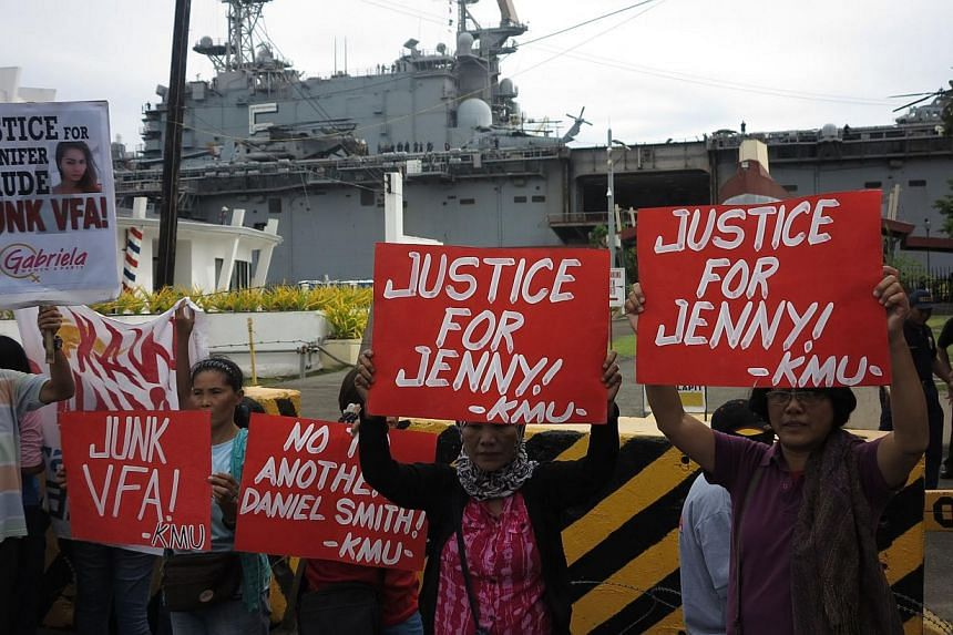 Relatives and supporters of murdered Filipino transgender Jeffrey Laude, also known as Jennifer, protest in front of the USS Peleliu, where murder suspect Private First Class Joseph Scott Pemberton is detained, at Subic port in Olongapo City, north o