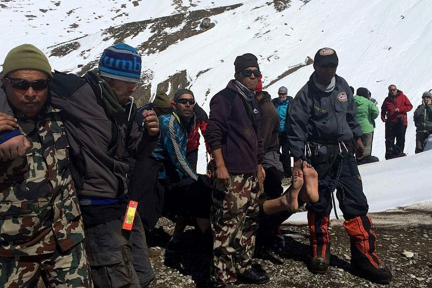 In this handout photograph released by the Nepal Army on Oct 17, 2014, a survivor injured in a snowstorm is carried on a stretcher by Nepal Army personnel to an army helicopter in the Manang district along the Annapurna Circuit Trek.Hopes faded