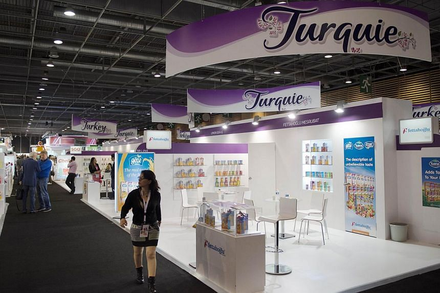 A visitor passes by the Turkish stand at the SIAL (Salon International de l'Agroalimentaire, Global Food Show), on Oct 19, 2014, in Villepinte, north-east of Paris.Acai, kimchi, black garlic and yuzu juice: countries are vying to conquer global