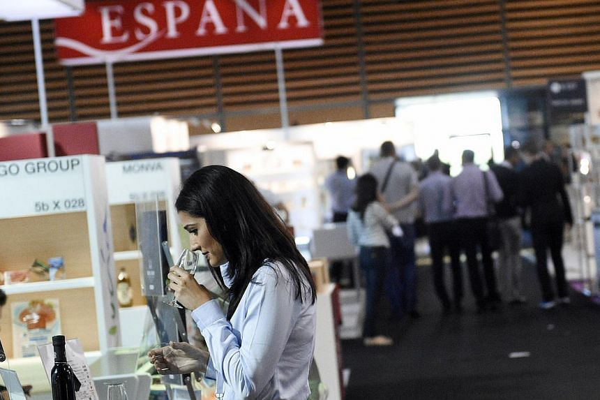A woman smells wine in a Spanish stand at the SIAL (Salon International de l'Agroalimentaire, Global Food Show), on Oct 19, 2014, in Villepinte, north-east of Paris. -- PHOTO: AFP