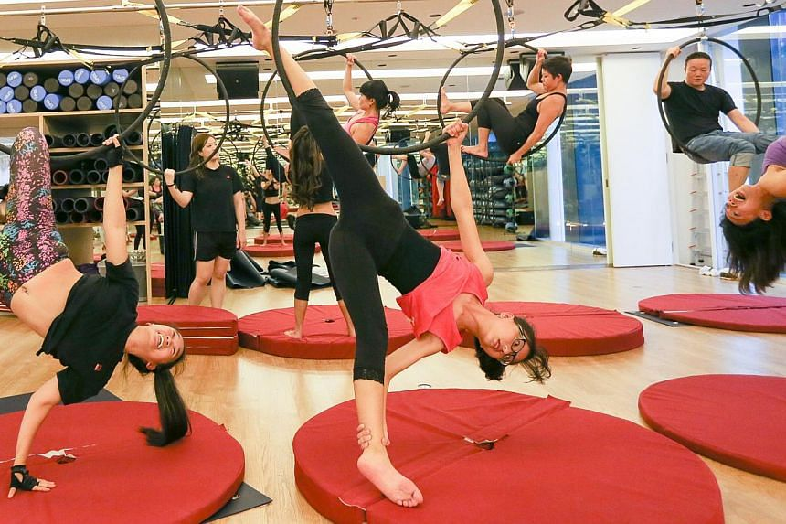 Participants at a twerking class grooving, twisting and gyrating; while others at an aerial hooping class (above) contort their limbs around steel hoops or bolts of silk hanging from the ceiling. --ST PHOTO: ONG WEE JIN