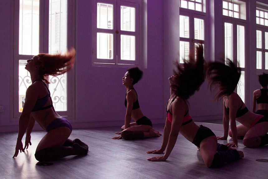 Participants at a twerking class (above) grooving, twisting and gyrating; while others at an aerial hooping class contort their limbs around steel hoops or bolts of silk hanging from the ceiling. --PHOTO: MILAN POLE DANCE STUDIO SINGAPORE