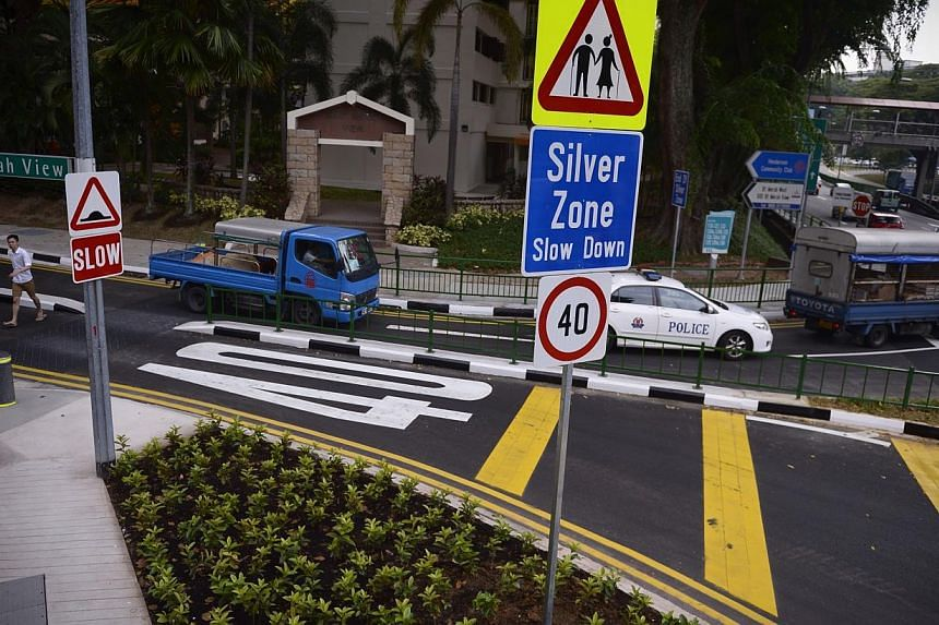 """Ramps for wheelchairs and """"look"""" ground markings (left) are some of the elder-friendly features at pedestrian crossings in Bukit Merah. Speed limit signs (right) and rumble stripes alert motorists that they are entering a Silver Zone."""