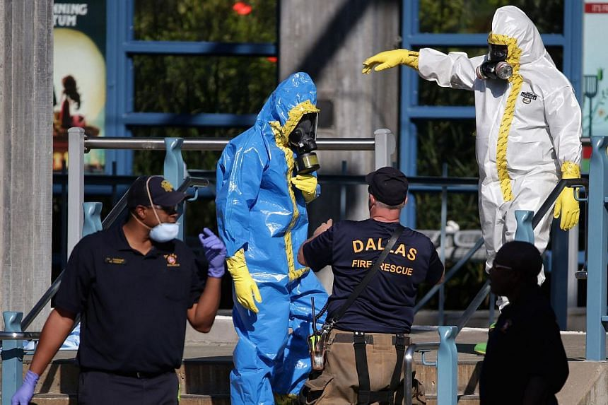 First responders wear full biohazard suits while responding to the report of a woman with Ebola-like symptoms at the Dallas Area Rapid Transit White Rock Station on Oct 18, 2014, in Dallas, Texas. Panic has been spreading across the country since a L