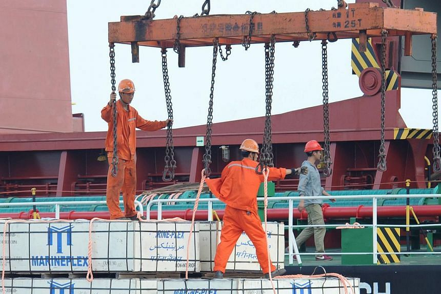 Workers load goods on a cargo ship at Lianyungang port in Lianyungang, east China's Jiangsu province on Aug 8, 2014. -- PHOTO: AFP