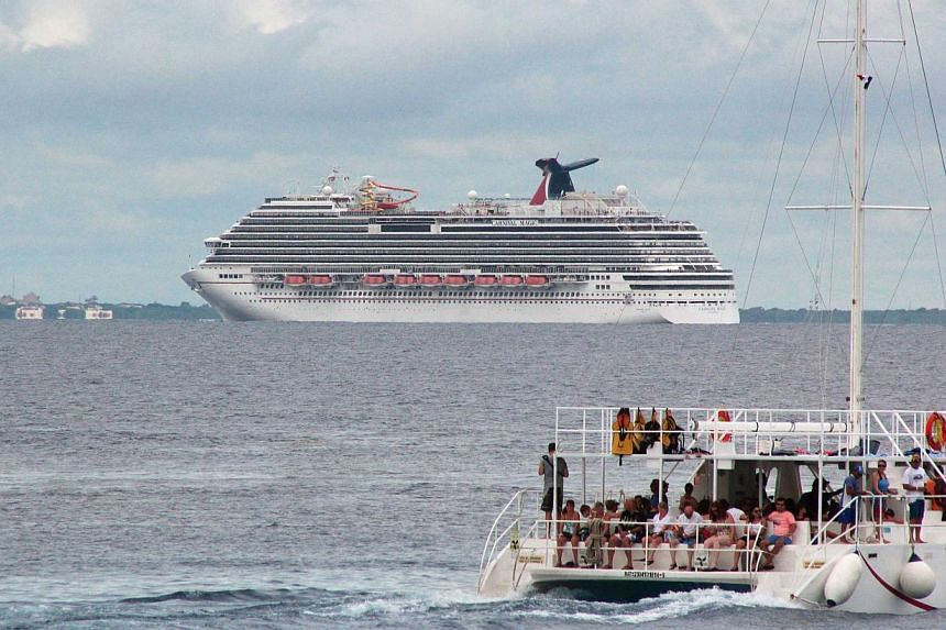 Tourists enjoy a ride on a catamaran as cruise ship Carnival Magic is seen near the shores of Cozumel on Oct 17, 2014.A cruise ship carrying a lab worker suspected of contact with Ebola returned to Texas on Sunday, as US media reported the woma
