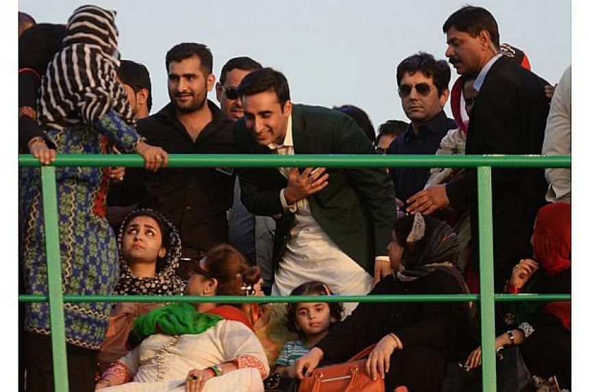 Bilawal Bhutto Zardari (centre) bows as he greets supporters during his arrival for a public gathering in Karachi on Oct 18, 2014. The son of slain former Pakistan premier Benazir Bhutto launched his formal political debut in a massive rally Saturday