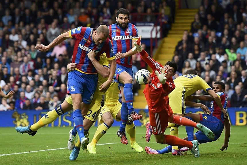 Crystal Palace's Brede Hangeland (left) has a header saved during their English Premier League soccer match against Chelsea at Selhurst Park in London Oct 18, 2014. -- PHOTO: REUTERS