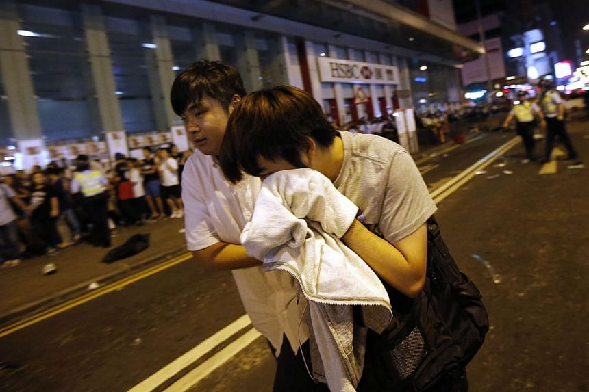 An injured pro-democracy protester is carried away after clashes with riot police at the Mongkok shopping district of Hong Kong Oct 19, 2014.  Violent clashes erupted early on Sunday in a Hong Kong protest hotspot as unarmed pro-democracy a