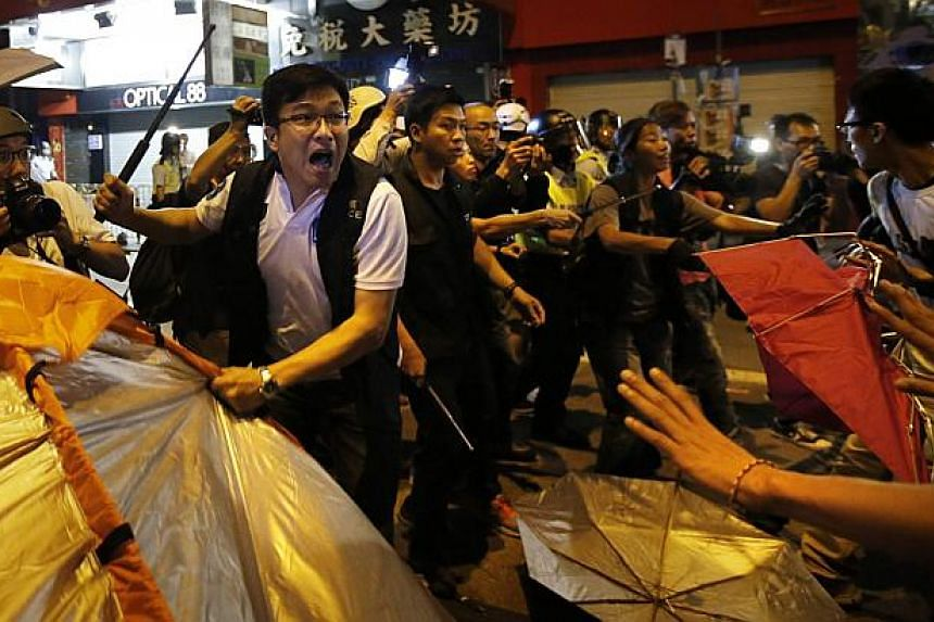 A police officer removes a tent from a protest site during a clash with pro-democracy protesters at the Mongkok shopping district of Hong Kong Oct 19, 2014.  Violent clashes erupted early on Sunday in a Hong Kong protest hotspot as unarmed
