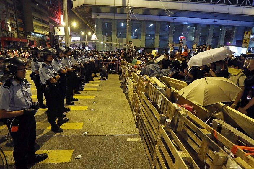 Riot police line up in front of protesters behind a barricade in the Mongkok shopping district of Hong Kong early Oct 19, 2014. Violent clashes erupted early on Sunday in a Hong Kong protest hotspot as unarmed pro-democracy activists once again