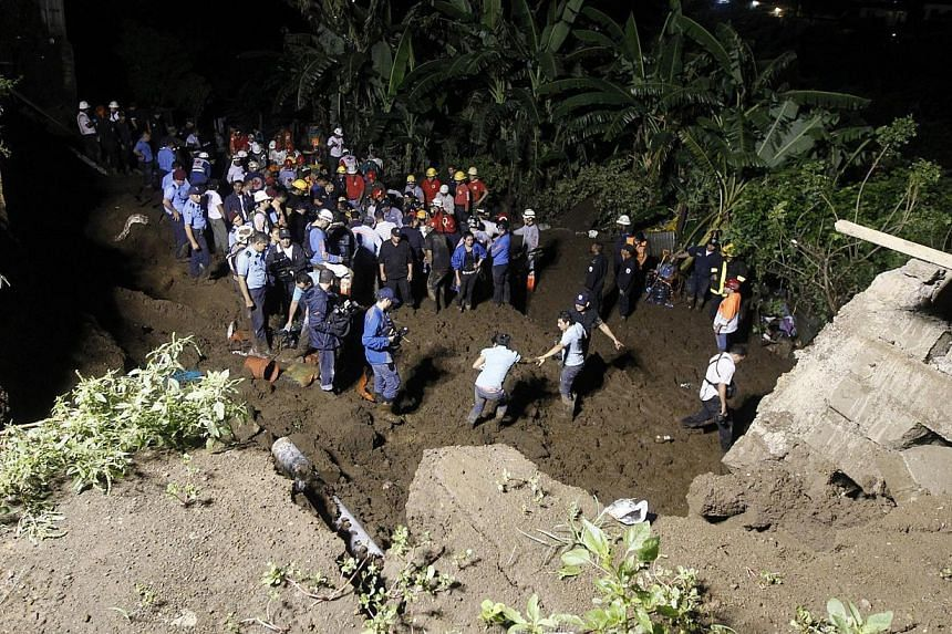 Rescue workers look for the bodies of eight people after the collapse of a perimeter wall at a residential area in Managua city on Oct 17, 2014. -- PHOTO: REUTERS
