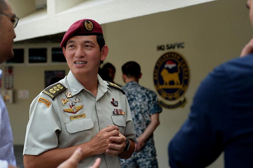 Colonel Mike Tan, who will head a newly formed Singapore Armed Forces (SAF) Volunteer Corps, having a brief chat with potential volunteers during a media briefing on Oct 10, 2014. -- ST PHOTO: JAMIE KOH
