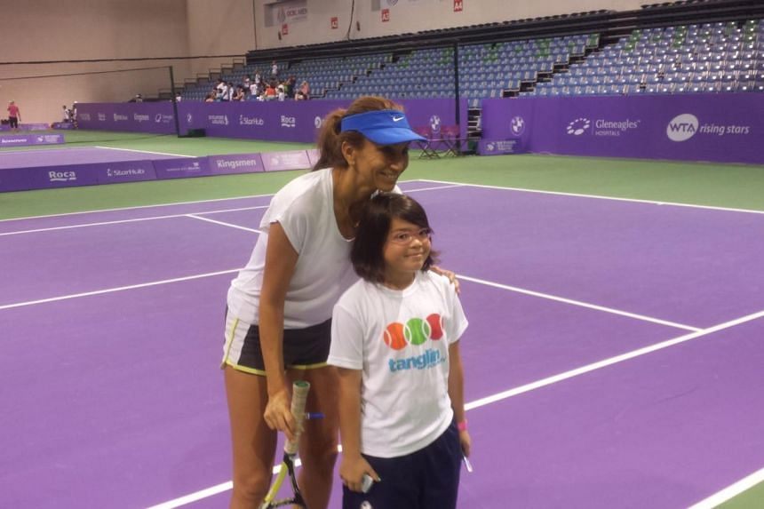 Grand Slam champion Iva Majoli poses with a fan after a friendly game of tennis. -- ST PHOTO: Daryl Chin