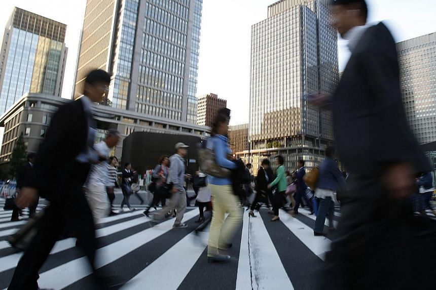People cross a street at Tokyo's business district on Oct 17, 2014. The junior partner in Japanese Prime Minister Shinzo Abe's coalition government on Monday called for steps to stimulate an economy hit by April's sales tax rise and to soften th