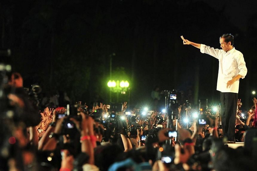Indonesia's new President Joko Widodo greets supporters on stage near the National Monument following his inauguration earlier in the day in Jakarta on Oct 20, 2014. -- PHOTO: REUTERS
