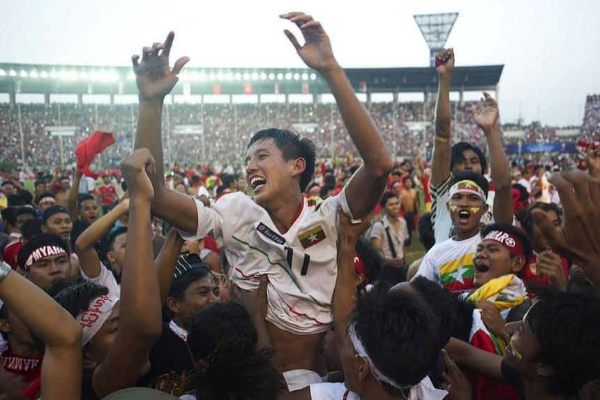 Than Paing of Myanmar (centre) is lifted up by fans as they celebrate after Myanmar won their AFC U-19 Championship quarter-final football match against the United Arab Emirates at Thuwanna stadium in Yangon on Oct 17, 2014. Asia's football gove