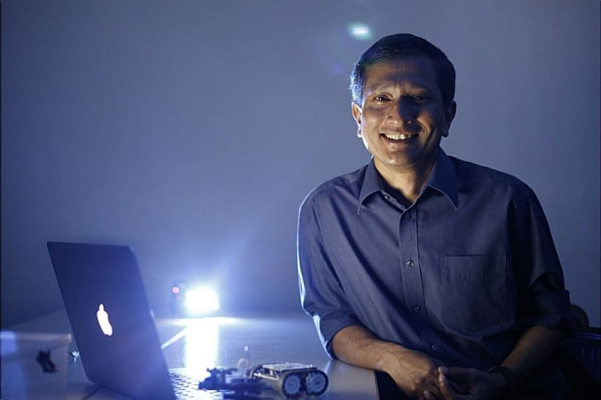 Singapore Minister for Environment and Water Resources Vivian Balakrishnan with some of his gadgets during a media interview at the NUS School of Computing geekcamp on 18 Oct, 2014.-- ST PHOTO: DESMOND LUI