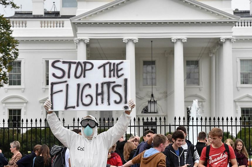 Jeff Hulbert from Annapolis, Maryland, dressed in a protective suit and mask holds a poster demanding for a halt of all flights from West Africa,as he protests outside the White House in Washington, DC on Oct 16, 2014.Weeks of worries about a p