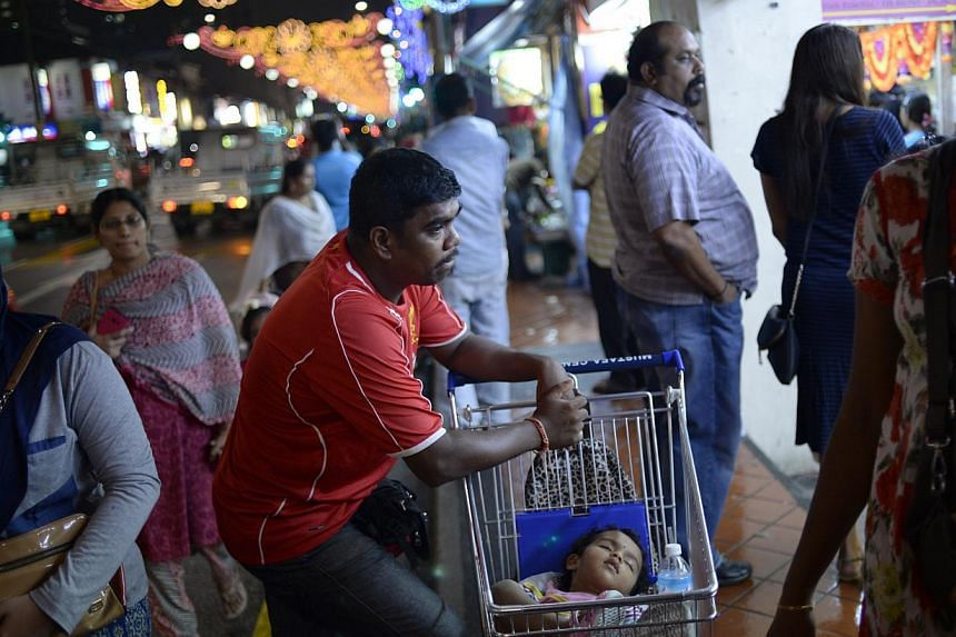 Mr Jaya Ganes, 39, waiting for his wife outside a sari shop as his two-year-old daughter Shajeenthana took a nap last Saturday. Deepavali, also known as the Festival of Lights, falls on Wednesday. Shoppers picking up deals in Little India, while a de