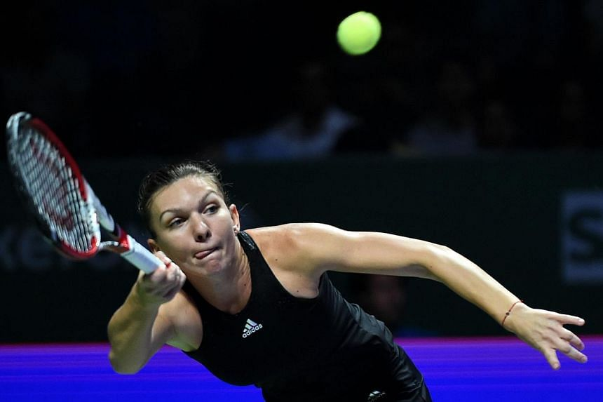 Simona Halep of Romania returns a ball to Eugenie Bouchard of Canada during the Women's Tennis Association (WTA) championships in Singapore on Oct 20, 2014. -- PHOTO: AFP